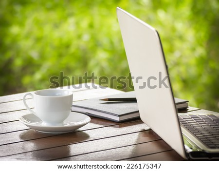 Cup of coffee and a laptop on dark wooden desk - stock photo