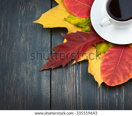 Cup of coffee and autumn leaves over dark wooden background - stock photo
