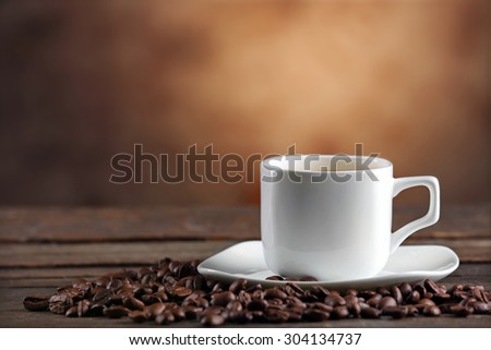 Cup of coffee and beans on blurred background - stock photo