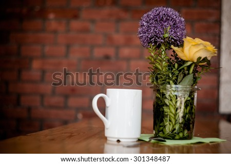Cup of coffee and beautiful flowers on wooden background - stock photo