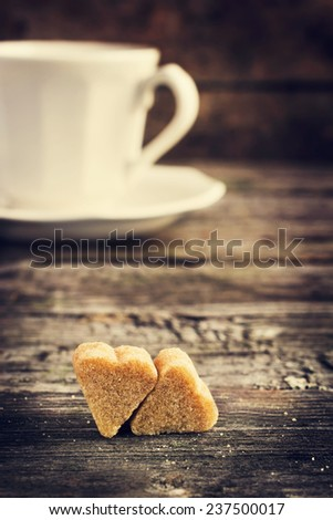 cup of coffee and brown cane sugar with shape of heart on old wooden table, selective focus, toned - stock photo