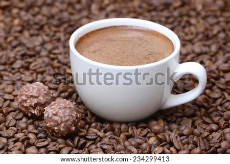cup of coffee and candies on a coffee beans background  - stock photo
