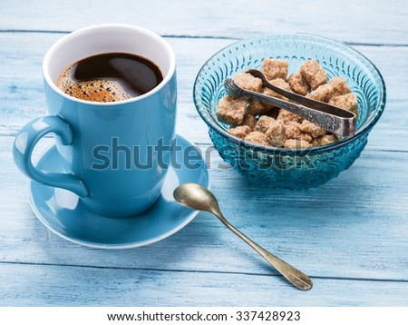 Cup of coffee and cane sugar cubes on old blue wooden table. - stock photo