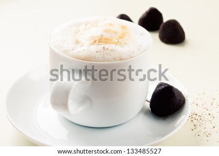 Cup of coffee  and chocolate truffles on white table - stock photo