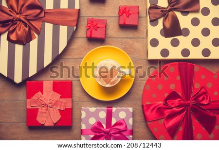 Cup of coffee and christmas gifts. - stock photo