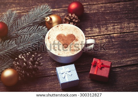 Cup of coffee and christmas toys with pine brench on wooden table. - stock photo