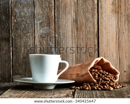 Cup of coffee and coffee beans in sack on wooden table - stock photo
