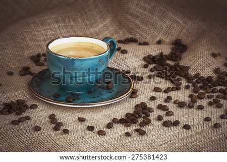 Cup of coffee and coffee beans on burlap background. Toned - stock photo