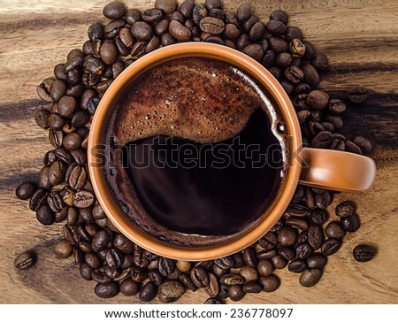 cup of coffee and coffee beans on old wooden table - stock photo