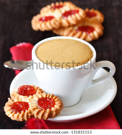 Cup of coffee and cookies with jam on a dark wooden background. - stock photo