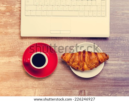 Cup of coffee and croissant near notebook on wooden table. - stock photo