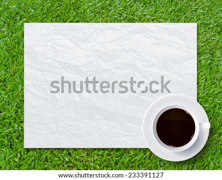 Cup of coffee and crumpled paper texture on green grass background. - stock photo