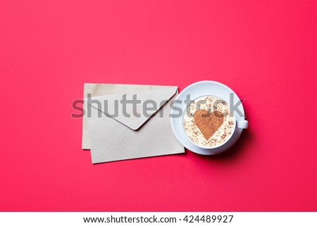 cup of coffee and envelopes on the red background - stock photo