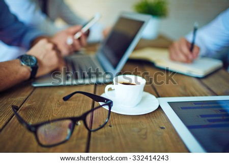 Cup of coffee and eyeglasses in working environment - stock photo