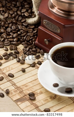 cup of coffee and grinder on table - stock photo