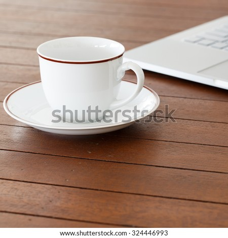 Cup of coffee and laptop computer on wooden background - stock photo