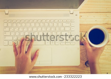 Cup of coffee and laptop on wooden table - stock photo