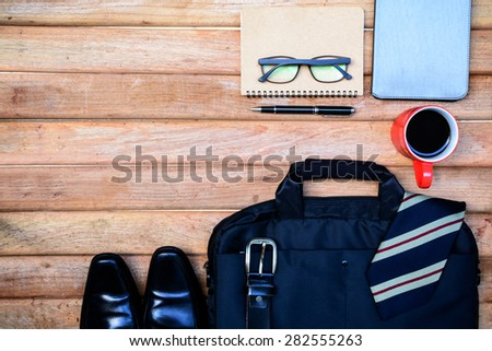Cup of coffee and men accessories on old wooden background with copy space - stock photo