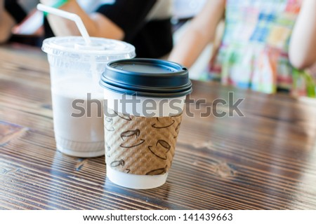 Cup of Coffee and Milk placed on table in cafe in front of people - stock photo