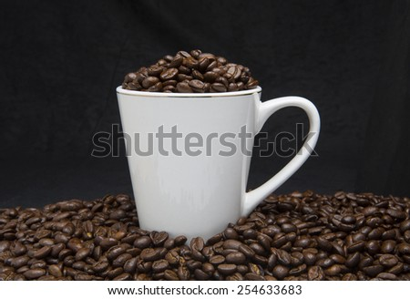 Cup of Coffee and multiple beans - stock photo