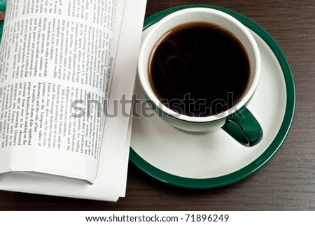 Cup of coffee and newspaper on dark desk - stock photo
