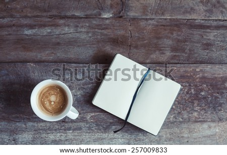 Cup of coffee and notebook with blank pages on a wooden background - photo taken from the top. Metaphor of a creative process. - stock photo