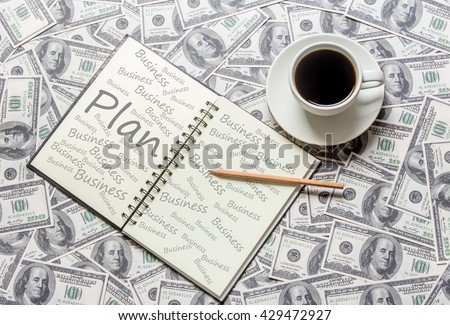 """Cup of coffee and open book with word """"business plan"""" - stock photo"""