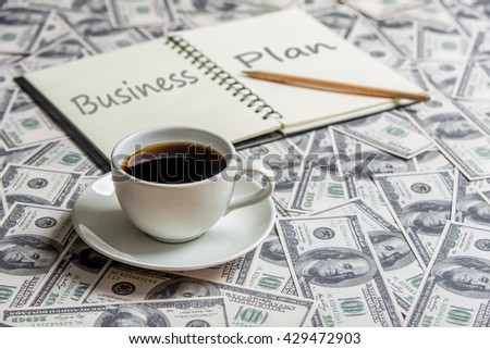 """Cup of coffee and open book with word """"business plan"""", focus a cup - stock photo"""