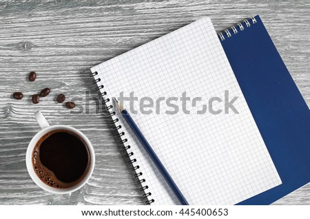 Cup of coffee and opened notepad on a wooden table, top view. Space for your text - stock photo