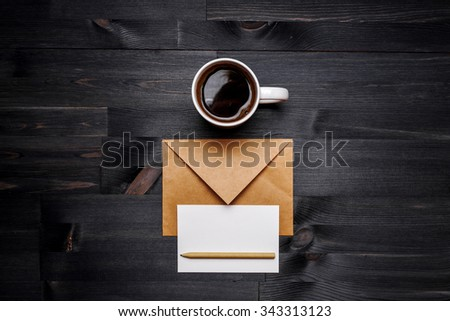 Cup of coffee and postal envelope with card on the wooden desk, top view at the studio - stock photo