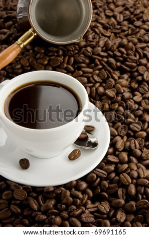 cup of coffee and pot on beans as background - stock photo