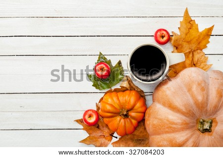 Cup of coffee and pumpkin with leafs on white wooden table - stock photo