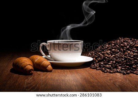 cup of coffee and roasted beans with croissants - stock photo