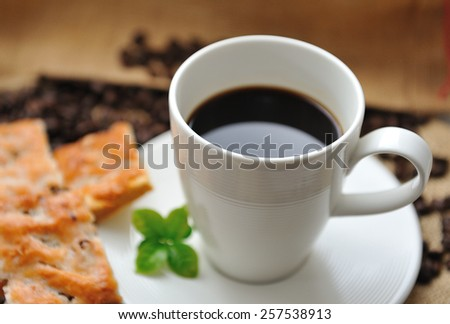 Cup of coffee and tasty cookie with coffee leaf - stock photo