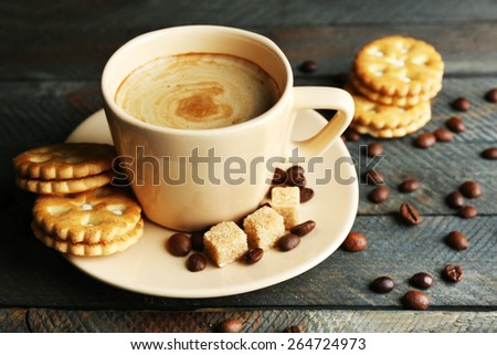 Cup of coffee and tasty cookies on wooden background - stock photo
