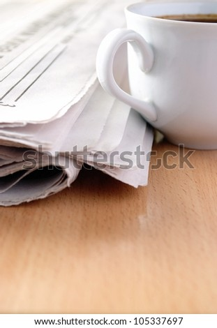 cup of coffee and the newspaper on the table - stock photo