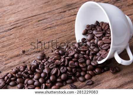 Cup of coffee beans on wood - stock photo