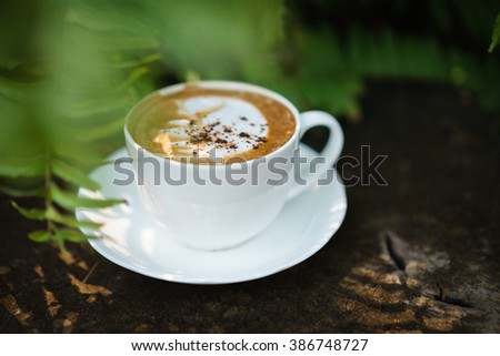Cup of coffee cappuccino art on wood floor with green leave frame - stock photo