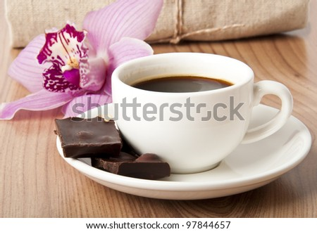 cup of coffee, chocolate and orchid on wooden background - stock photo
