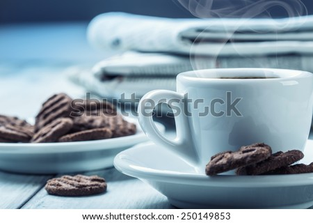Cup of coffee , chocolate biscuits and the background newspaper. Coffee break.  - stock photo