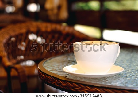 Cup of coffee closeup on the table. Brown caffeine drink in cafe. Aroma hot black espresso, cappuccino with foam on breakfast in the morning in cafe or restaurant. Background with fresh latte.  - stock photo
