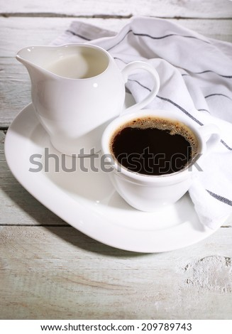 Cup of coffee, creamer on color wooden background - stock photo