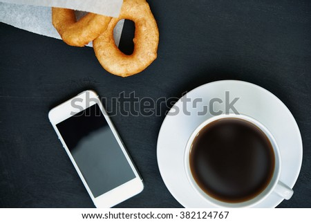 cup of coffee, doughtuts in paper bag and white smartphone. top view - stock photo