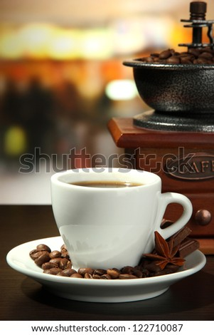cup of coffee, grinder and coffee beans in cafe - stock photo