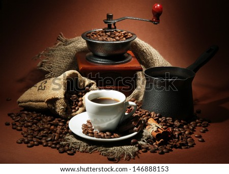 cup of coffee, grinder, turk and coffee beans on brown background - stock photo