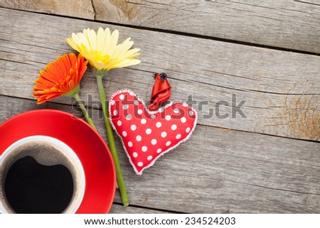 Cup of coffee, heart toy and gerbera flowers on wooden table with copy space - stock photo
