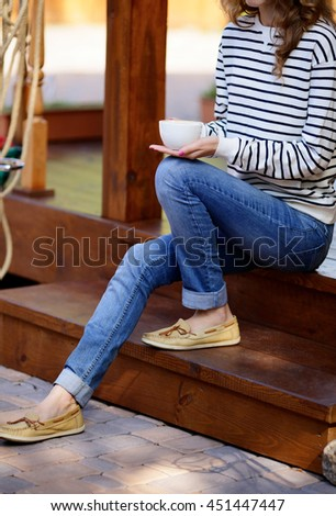 Cup of coffee in hands woman which sits on the wooden steps the porch - stock photo