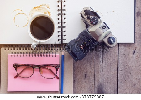 Cup of coffee in morning with old camera and note book on Wood Background - stock photo