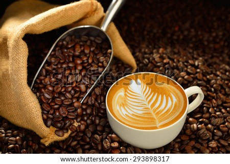 Cup of coffee latte and coffee beans on wooden table - stock photo