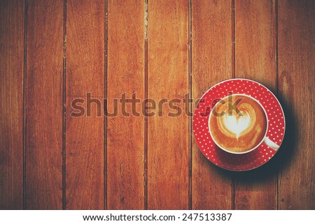 cup of coffee latte art on the wooden desk vintage color - stock photo